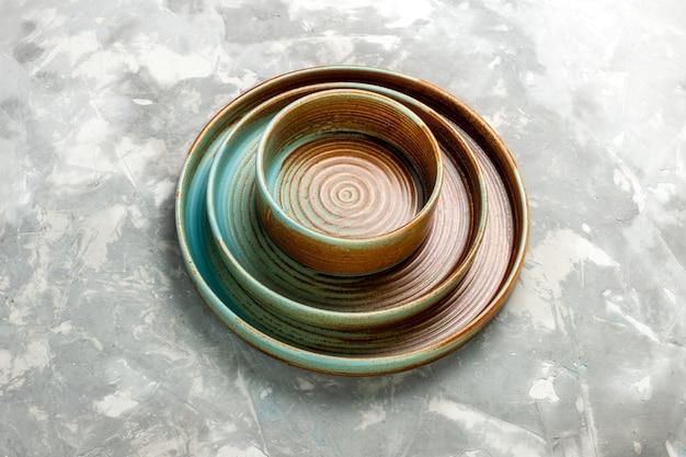 Demi-vue de dessus assiettes rondes marron de différentes tailles vides isolés sur un bureau gris clair.