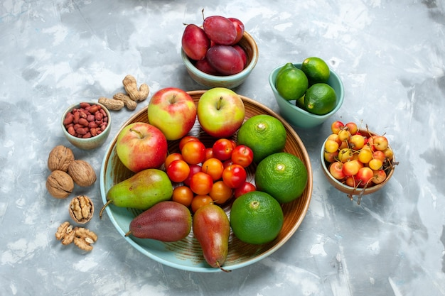 Demi-vue de dessus de composition de fruits pommes poires mandarines et prunes sur un bureau blanc.