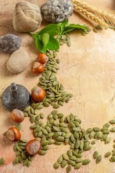 Demi-vue de dessus de noisettes fraîches avec des graines de citrouille sur la photo couleur de l'écrou de bureau en bois
