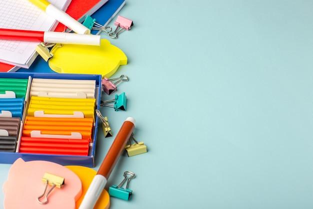 Demi-vue de dessus de pâte à modeler colorée avec des cahiers sur le mur bleu couleur école enfants livre