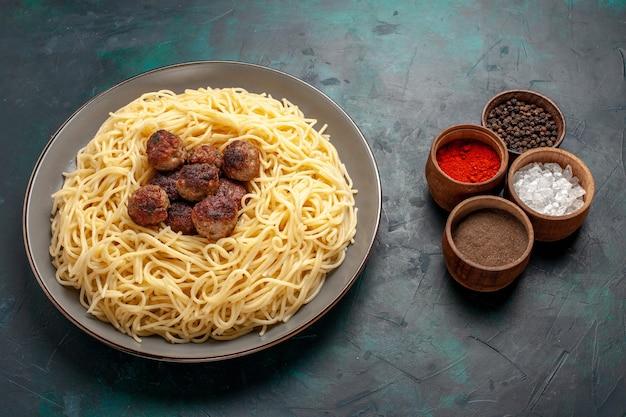 Demi-vue de dessus de pâtes italiennes cuites avec des boulettes de viande et des assaisonnements sur une surface bleu foncé