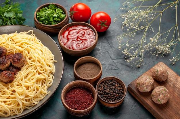 Demi-vue de dessus des pâtes italiennes cuites avec différents assaisonnements sur la surface bleu foncé