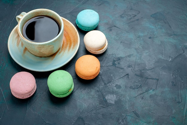 Demi-vue de dessus tasse de thé avec des macarons français sur fond bleu foncé.