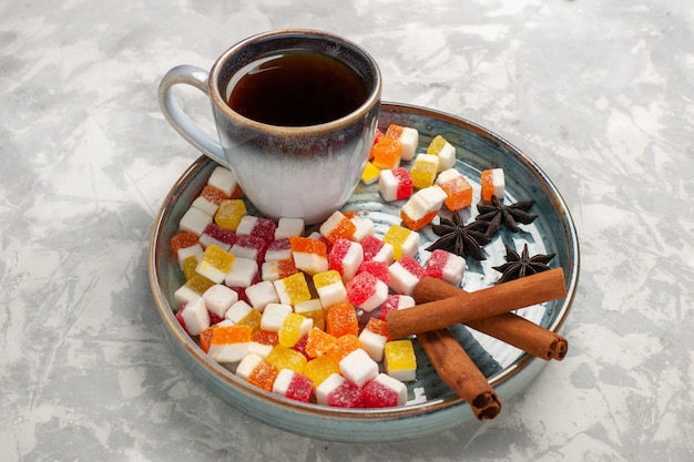 Demi-vue de dessus tasse de thé avec de la marmelade et de la cannelle sur une surface blanche claire