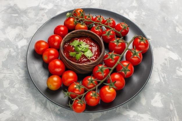 Demi-vue de dessus tomates cerises fraîches à l'intérieur de la plaque sur la surface blanche