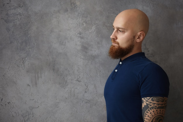 Demi-vue de profil de beau hipster caucasien élégant avec tête rasée et longue barbe touffue posant contre un mur blanc gris avec espace de copie pour votre contenu publicitaire