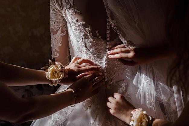 Demoiselle d'honneur aidant mariée à attacher un corset et obtenir sa robe, préparer la mariée le matin pour le jour du mariage.