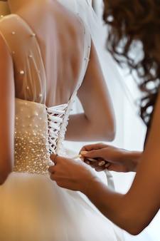 Demoiselle d'honneur aidant mariée à attacher un corset