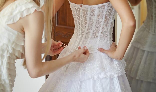 Demoiselle d'honneur aidant la mariée