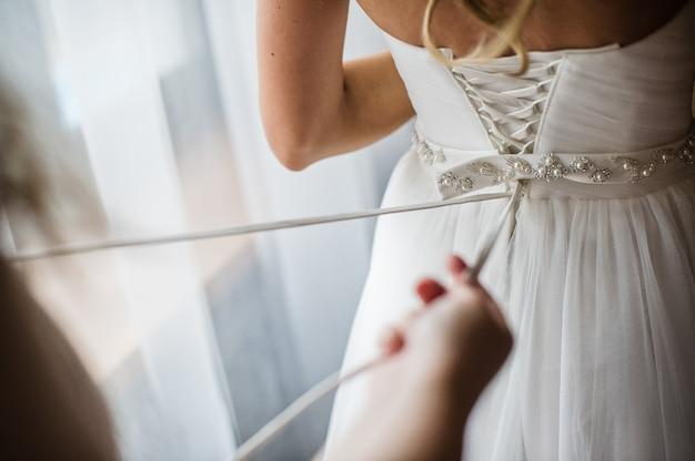 Demoiselle d'honneur aide à porter une robe de mariée