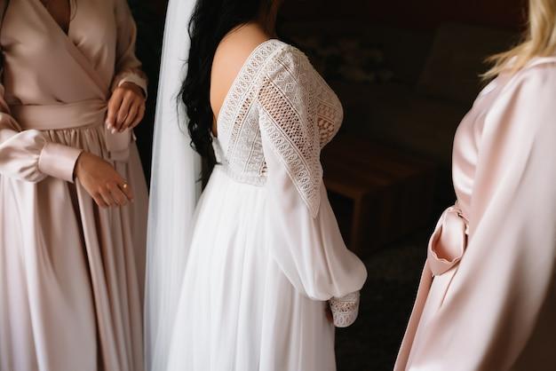 Demoiselle d'honneur prépare la mariée pour le jour du mariage