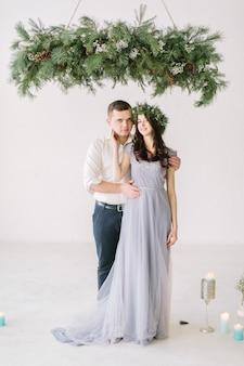 Demoiselle d'honneur en robe grise et garçon d'honneur debout près du mur blanc après la cérémonie de mariage