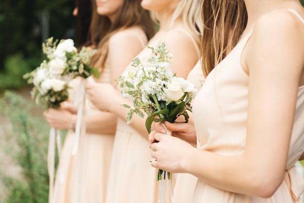 Demoiselles d'honneur glorieuses en robes légères tenant de belles fleurs