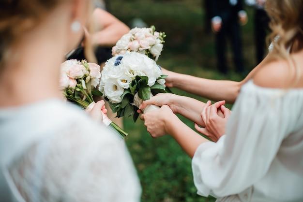 Demoiselles d'honneur en robes blanches tenant des bouquets de roses