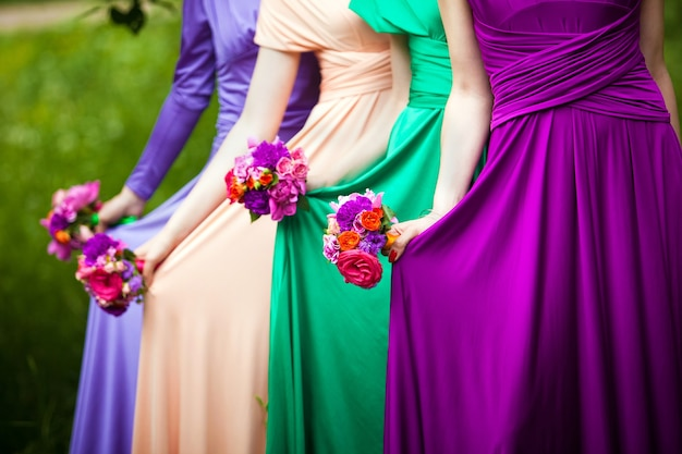 Demoiselles d'honneur en robes colorées avec des bouquets de fleurs