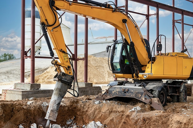 Démolition professionnelle de structures en béton armé à l'aide d'un marteau hydraulique industriel avec excavatrice. tiges de ferrures métalliques. épave et émiettage de béton.