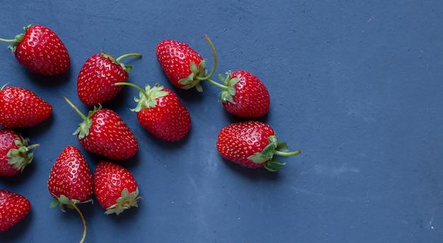 Démonstration de fraises sur une table bleue.