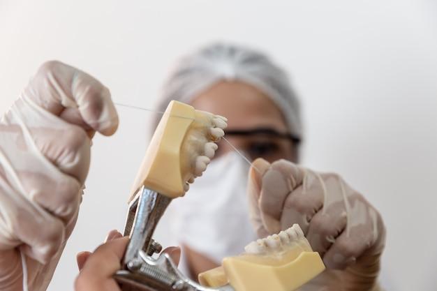 Démonstration de l'utilisation du fil dentaire. dentiste enseignant au patient comment utiliser la soie dentaire.