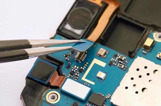 Démontage du smartphone montrant le tableau électrique à l'intérieur. le téléphone est en train de réparer