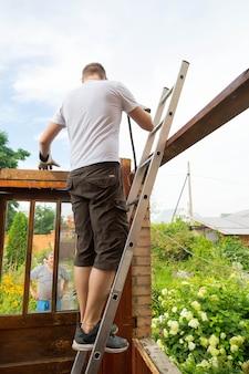 Démontage du toit. le travailleur enlève les vieilles planches du toit, la maison est en cours de rénovation.