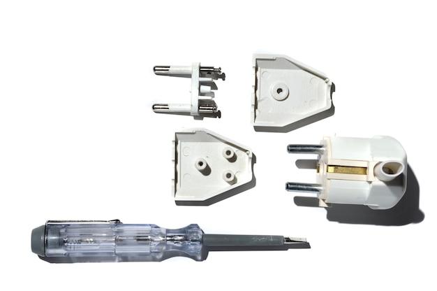 Démontage de la fiche électrique à l'aide d'un tournevis testeur.