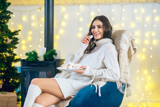 La dent sucrée. femme en vêtements blancs, manger de la guimauve et à apprécier