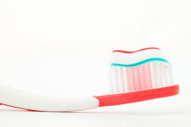 Dentifrice sur une brosse à dents rouge