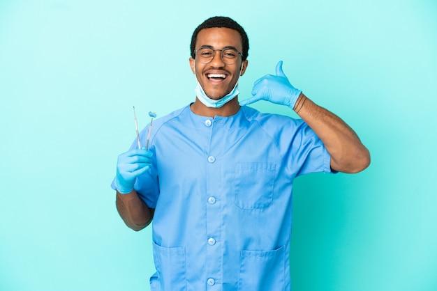 Dentiste afro-américain tenant des outils sur fond bleu isolé faisant un geste téléphonique. rappelle-moi signe