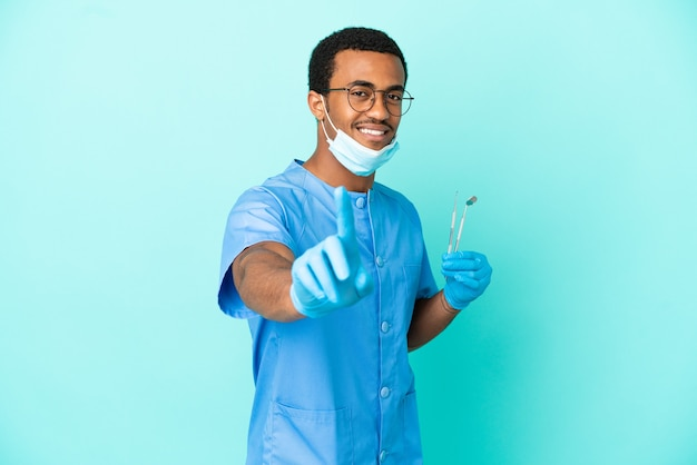 Dentiste afro-américain tenant des outils sur fond bleu isolé montrant et levant un doigt