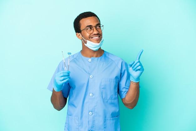 Dentiste afro-américain tenant des outils sur fond bleu isolé pointant vers une excellente idée