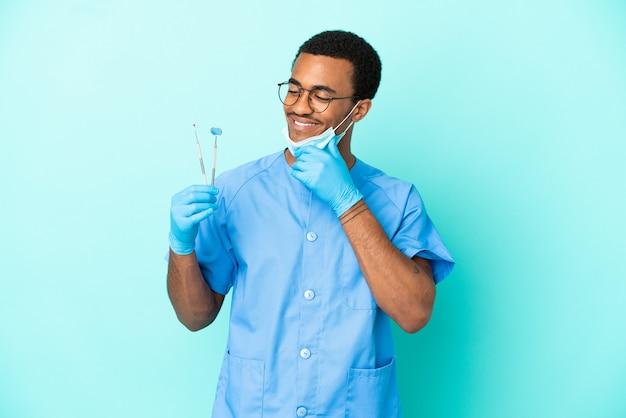 Dentiste afro-américain tenant des outils sur fond bleu isolé regardant sur le côté et souriant