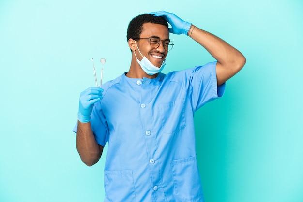 Dentiste afro-américain tenant des outils sur fond bleu isolé souriant beaucoup