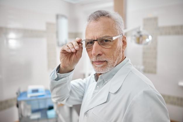 Dentiste âgé sûr de lui touchant ses lunettes et souriant tout en se tenant dans son bureau et en regardant la caméra