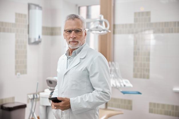 Dentiste âgé sérieux tenant un smartphone debout dans sa clinique et regardant la caméra