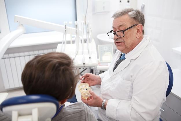 Dentiste âgé de sexe masculin travaillant dans sa clinique, parlant au patient