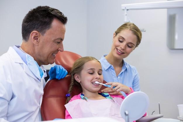 Dentiste aidant un jeune patient lors du brossage des dents
