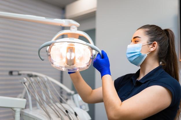 Le dentiste ajuste la lampe dentaire en fonction de ses besoins
