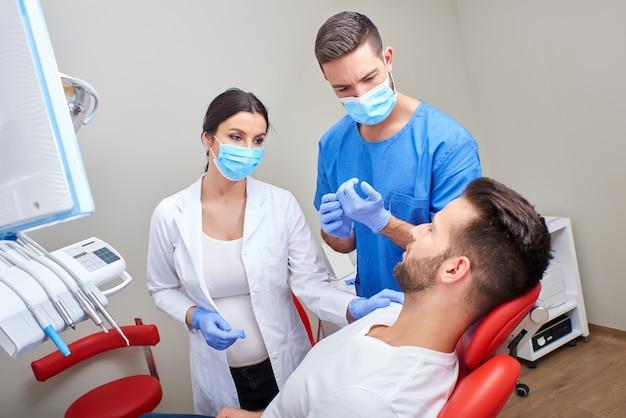 Un dentiste et un assistant avec le patient