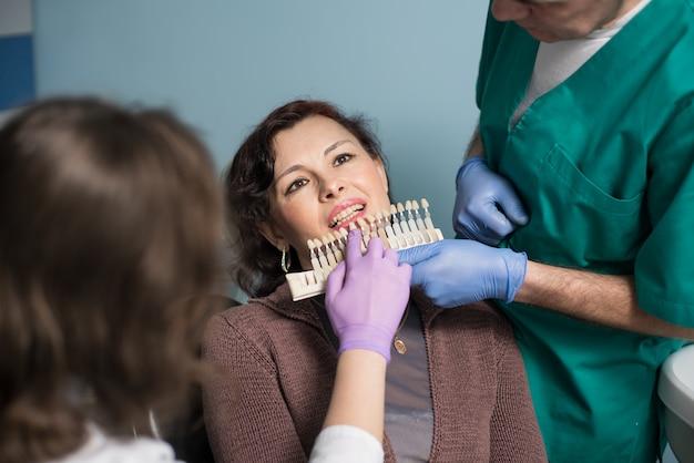 Dentiste avec assistant et patiente vérifiant et sélectionnant la couleur des dents au bureau de la clinique dentaire