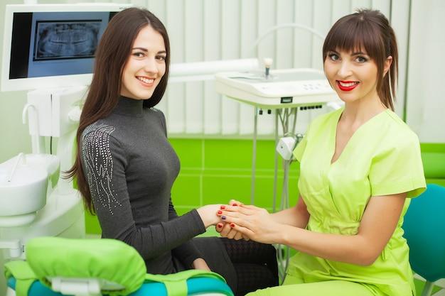 Dentiste en cabinet dentaire discutant avec une patiente et se préparant pour le traitement