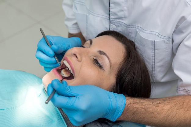 Dentiste comparant la couleur des dents des patients avec un échantillonneur
