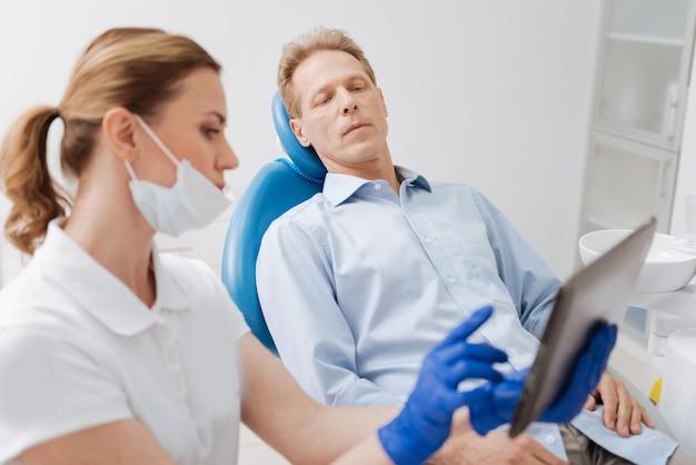 Dentiste compétent attentif et délicat s'assurant que le patient comprend tout tout en illustrant son diagnostic avec les données sur son gadget