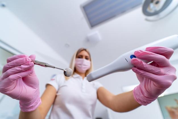 Le dentiste détient des instruments médicaux spécifiques pour l'examen du patient. des yeux du patient.