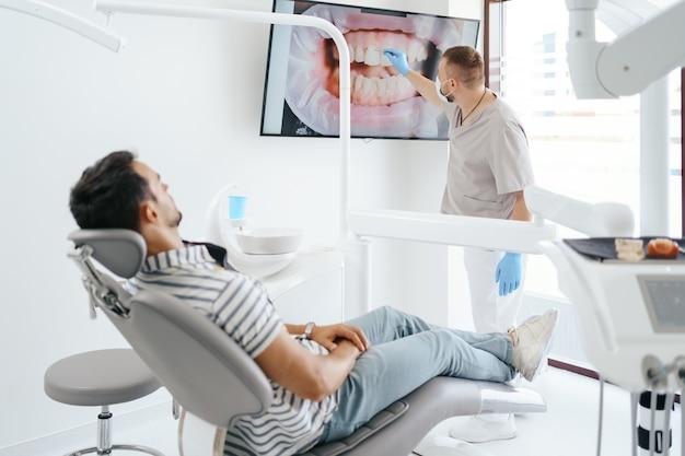 Dentiste discutant avec un patient allongé montrant l'image de ses dents à l'écran
