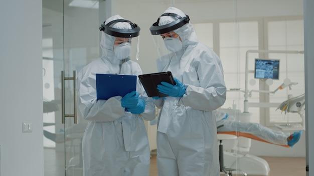 Dentiste donnant le comprimé à l'infirmière dentaire avant la consultation