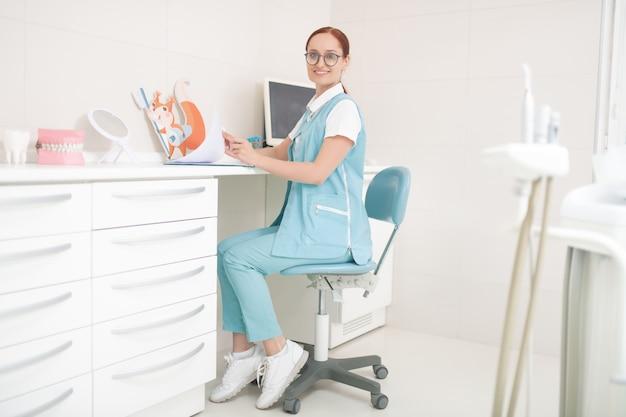 Dentiste enfant joyeux. dentiste joyeux enfant portant des lunettes assis dans son cabinet dentaire à la table
