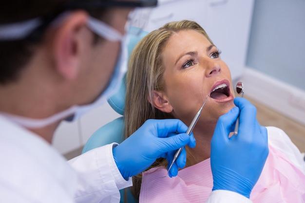Dentiste examinant la bouche de la femme à la clinique