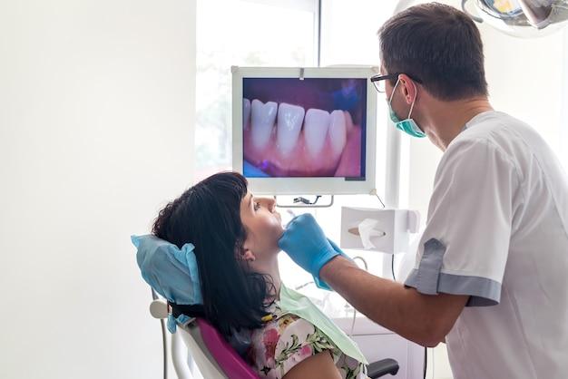 Dentiste examinant les dents du patient avec caméra intra-orale