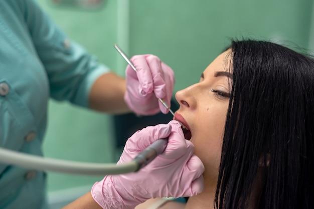 Dentiste examinant les dents du patient avec miroir dans des gants de protection
