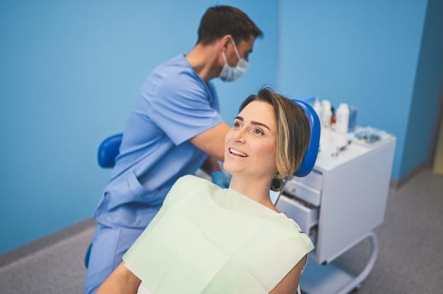 Dentiste examinant les dents d'un patient à l'aide d'un équipement dentaire en cabinet dentaire. concept de stomatologie et de soins de santé. jeune beau docteur masculin en masque facial médical jetable, femme heureuse souriante